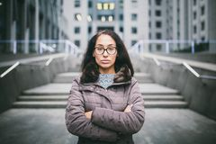 Beautiful young woman of European ethnicity with long brunette hair with grave emotion, wearing glasses and a coat stands against royalty free stock image