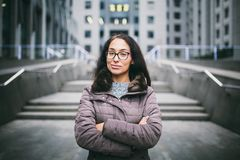 Beautiful young woman of European ethnicity with long brunette hair with grave emotion, wearing glasses and a coat stands against royalty free stock images