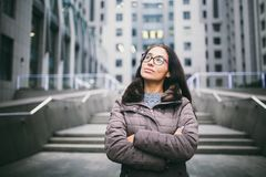 Beautiful young woman of European ethnicity with long brunette hair looking to side and up, wearing glasses and coat stands on bac stock photo