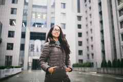 Beautiful young woman of European ethnicity with long brunette hair with a toothy smile, wearing glasses and a coat stands against stock photos
