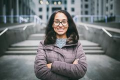Beautiful young woman of European ethnicity with long brunette hair with a toothy smile, wearing glasses and a coat stands against royalty free stock photo