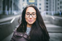 Beautiful young woman of European ethnicity with long brunette hair with a toothy smile, wearing glasses and a coat stands against royalty free stock image