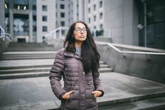 Beautiful young woman of European ethnicity with long brunette hair, wearing glasses and a coat stands against backdrop of a busin stock photo