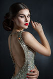 Beautiful young woman in an evening dress crystal. Perfect beauty, red lips, bright makeup. Twinkling sparkling stones on dress. Hair in a beautiful hairstyle stock photo