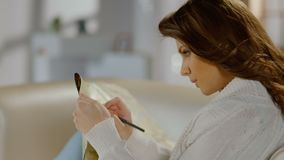 Beautiful young woman examining map, making notes with pencil. Stock footage stock video