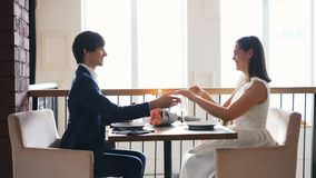 Beautiful young woman is excited about marriage proposal in restaurant while her boyfriend is talking then putting ring. Beautiful young woman is excited about stock video footage