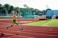 Beautiful young woman exercise jogging and running on athletic track on stadium. stock photo