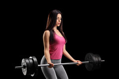 Beautiful young woman exercising with a barbell. On black background Stock Photo