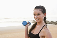 Beautiful young woman exercising on beach Stock Photography
