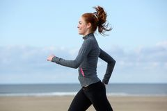 Beautiful young woman exercising by the beach Stock Images