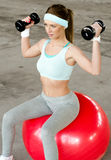 Beautiful young woman exercising with dumbbells and fitness ball Stock Photos