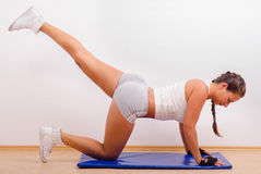 Beautiful young woman exercising. On the floor Stock Photo
