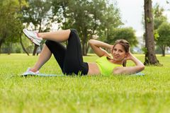 Beautiful young woman exercising on a grass Royalty Free Stock Photo