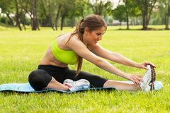 Beautiful young woman exercising on a grass Royalty Free Stock Images