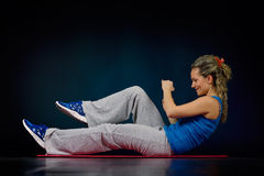 Beautiful young woman exercising in the gym. Beautiful smiling woman exercising in the gym Stock Photo
