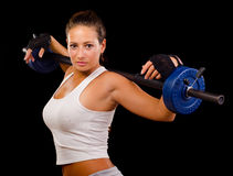 Beautiful young woman exercising with weights. Isolated on black Royalty Free Stock Images