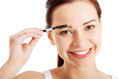 Beautiful young woman with eye brush. Stock Photography