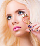 Beautiful young woman with eyelash curler Royalty Free Stock Image