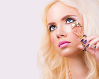 Beautiful young woman with eyelash curler Stock Photos