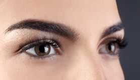 Beautiful young woman with eyelash extensions. On grey background, closeup Stock Images