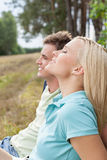 Beautiful young woman with eyes closed relaxing by man in forest. Beautiful young women with eyes closed relaxing by men in forest Stock Photo