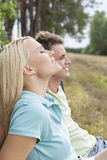 Beautiful young woman with eyes closed relaxing by man in forest Royalty Free Stock Photos