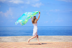 Beautiful young woman with fabric running on quay. Summer Stock Images