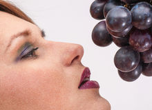 A Beautiful young woman face with grape Royalty Free Stock Image