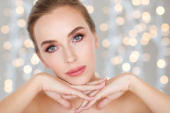 Beautiful young woman face and hands over lights Royalty Free Stock Photography