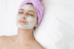 Beautiful young woman with face mask. Young woman with face mask in spa salon Stock Photography