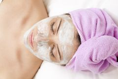 Beautiful young woman with face mask. In spa salon Royalty Free Stock Photos