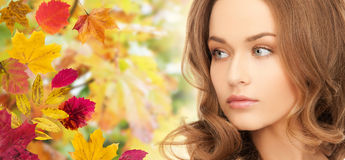 Beautiful young woman face over autumn leaves Royalty Free Stock Photos