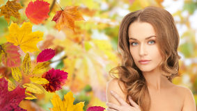 Beautiful young woman face over autumn leaves Royalty Free Stock Photo