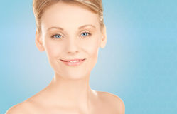 Beautiful young woman face over blue background Stock Photos