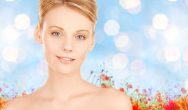 Beautiful young woman face over blue background Royalty Free Stock Photography