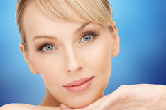 Beautiful young woman face over blue background stock images