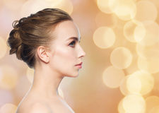 Beautiful young woman face over holidays lights Royalty Free Stock Photo