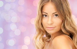 Beautiful young woman face over pink lights Royalty Free Stock Images
