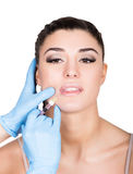 Beautiful young woman face and syringe making injection. Isolated over white background. Royalty Free Stock Image