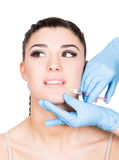 Beautiful young woman face and syringe making injection. Isolated over white background. Royalty Free Stock Photos