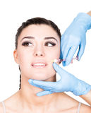 Beautiful young woman face and syringe making injection. Isolated over white background. Royalty Free Stock Images