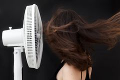 Beautiful young woman face to electric fan enjoying cold wind to refreshing up Royalty Free Stock Photo