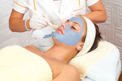 Beautiful young woman with facial mask Stock Images