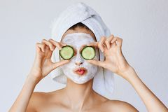 Beautiful young woman with facial mask on her face holding slices of cucumber. Skin care and treatment, spa, natural beauty and