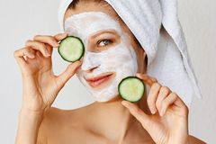 Beautiful young woman with facial mask on her face holding slices of cucumber. Skin care and treatment, spa, natural beauty and royalty free stock photos