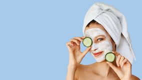 Beautiful young woman with facial mask on her face holding slices of cucumber. Skin care and treatment, spa, natural beauty and stock image
