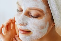 Beautiful young woman with facial mask on her face. Skin care and treatment, spa, natural beauty and cosmetology concept. Over white background royalty free stock images