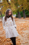 Beautiful young woman at fall. Beautiful young woman in polka dot trench at fall royalty free stock photography