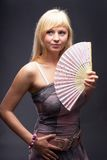 Beautiful young woman with fan Stock Photo