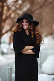 Beautiful young woman in fashion black coat, hat,  lace dress an. D boots with high heels smilling outside. Vogue style Stock Image